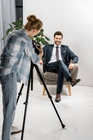 back view of young photographer taking pictures of handsome smiling businessman in office