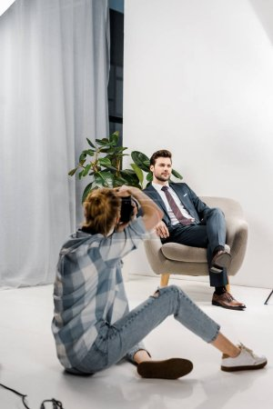 back view of female photographer with camera photographing handsome male model in studio