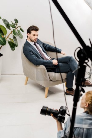 high angle view of young photographer and handsome model working together in photo studio