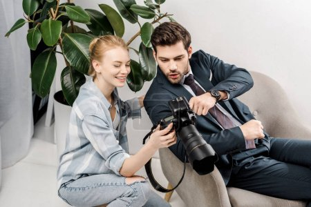 smiling female photographer and surprised handsome businessman using camera in photo studio