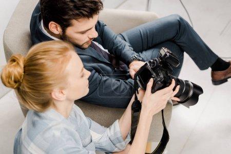 Photo pour Vue de la forte inclinaison du photographe et modèle à l'aide d'appareil photo en studio - image libre de droit