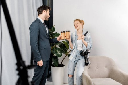 Photo for Smiling photographer and handsome model holding paper cups and talking in photo studio - Royalty Free Image