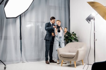female photographer and young businessman holding paper cups and checking photos on camera in studio