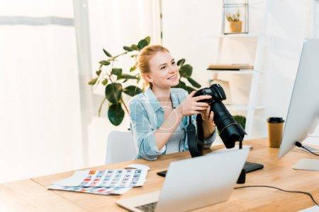 Photo pour Belle souriante jeune femme photographe tenant l'appareil alors qu'il travaillait au bureau - image libre de droit