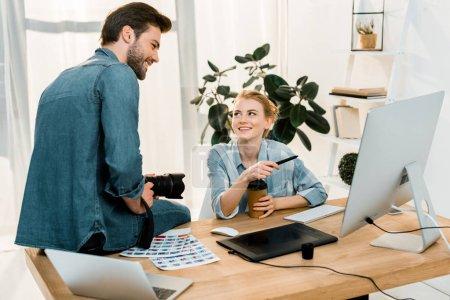 Foto de Sonriente joven fotógrafos que trabajan con dispositivos digitales en el lugar de trabajo - Imagen libre de derechos