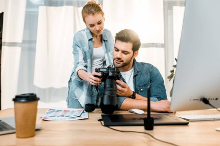 Photo for Professional smiling young photographers using photo camera together in office - Royalty Free Image