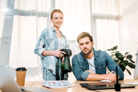 Foto de Fotógrafos jóvenes profesionales trabajando juntos y sonriendo a la cámara en la oficina - Imagen libre de derechos