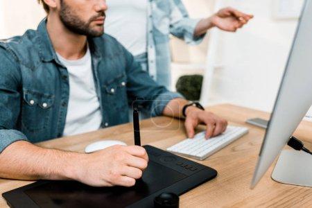 Photo pour Recadrée tir de mâle retoucher à l'aide de tablette tout en workign avec une collègue au bureau - image libre de droit
