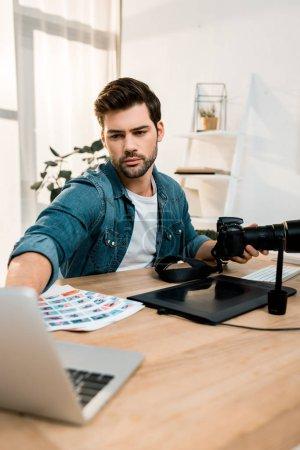 Photo pour Beau jeune photographe à l'aide de la caméra et l'ordinateur portable au lieu de travail - image libre de droit