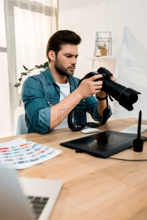 handsome young photographer using camera at workplace