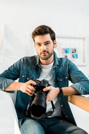 handsome young photographer holding photo camera in office