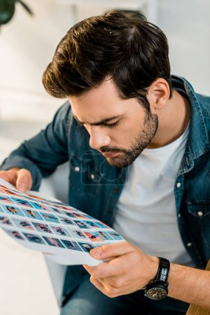 handsome young photographer looking at pictures in office