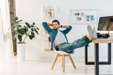 Foto de Retoucher joven guapo sentado con las manos a la cabeza y las piernas en la mesa de trabajo - Imagen libre de derechos