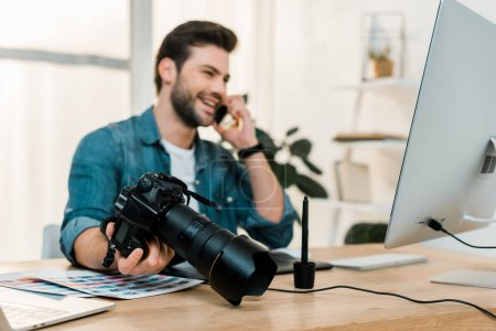 happy young photographer holding camera and talking by smartphone at work desk