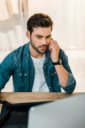 handsome young man retouching photos at workplace
