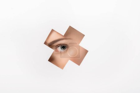 Photo for Partial view of beautiful girl looking at camera through cross shaped hole on white - Royalty Free Image