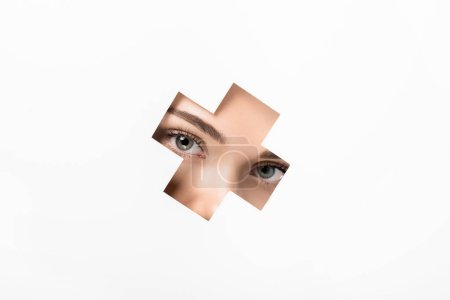 partial view of attractive girl looking at camera through cross shaped hole on white