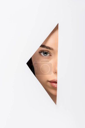 partial view of attractive girl looking at camera through hole on white