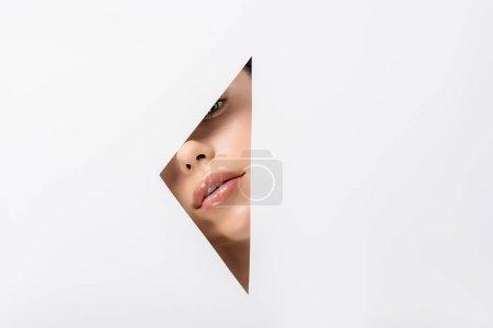 Photo pour Attrayant jeune femme regardant caméra à travers le trou sur blanc - image libre de droit