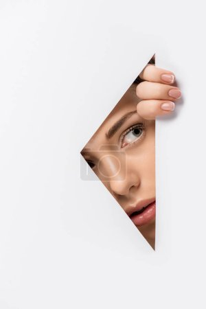 Photo for Young woman looking away through hole on white - Royalty Free Image
