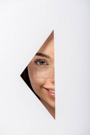 Photo pour Belle jeune femme souriant à la caméra à travers le trou sur blanc - image libre de droit