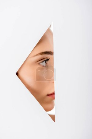 profile of beautiful young woman looking away, view through hole on white