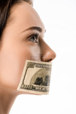 close-up view of woman with dollar banknote on mouth looking away isolated on white