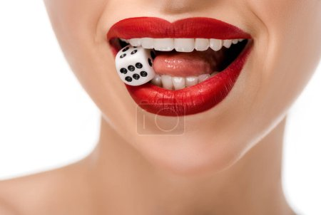 close-up partial view of young woman holding dice in teeth isolated on white