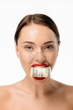 beautiful young woman holding rolled dollar banknotes in teeth and looking at camera isolated on white