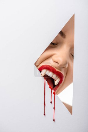 cropped shot of woman with vampire teeth and blood biting through hole on white