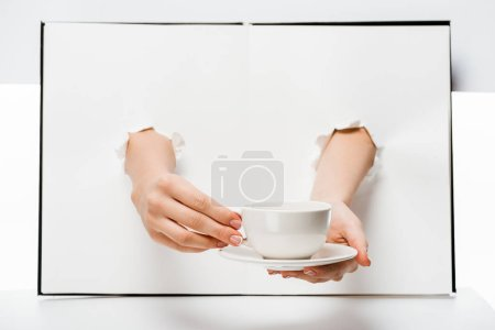 cropped shot of woman holding cup and saucer through holes on white