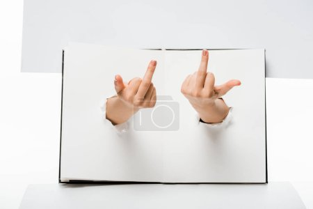 cropped shot of woman showing middle fingers through holes on white