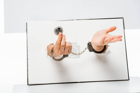 partial view of woman in handcuffs holding bitcoin through holes on white