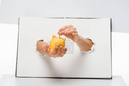 cropped shot of woman putting coin into yellow piggy bank through holes on white