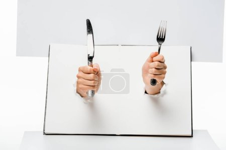 Photo for Partial view of woman holding fork and knife through holes on white - Royalty Free Image