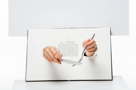 cropped shot of woman holding fork and knife through holes on white