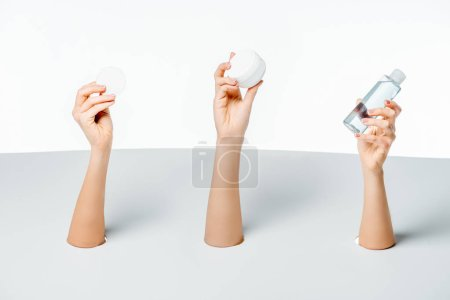 cropped shot of women holding cream, lotion and cotton pad through holes on white