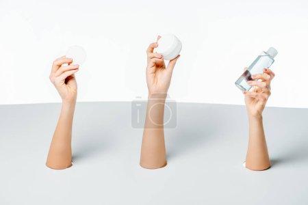 recortar el plano de mujeres sosteniendo crema, loción y algodón cojín a través de agujeros en blanco