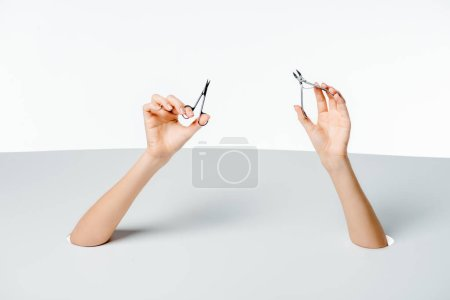 cropped shot of woman holding manicure tools through holes on white