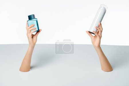 cropped shot of woman holding containers with beauty products through holes on white