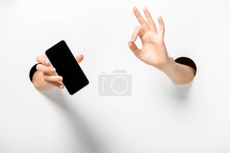 cropped image of woman holding smartphone with blank screen and showing okay gesture through holes on white