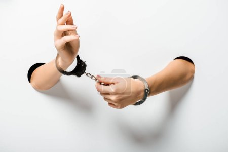cropped image of woman in handcuffs holding hands through holes on white