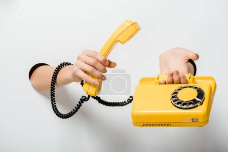 Photo for Cropped image of woman holding retro yellow stationary telephone through holes on white - Royalty Free Image