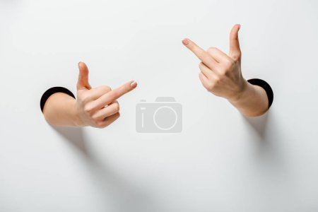 cropped image of woman showing middle fingers through holes on white