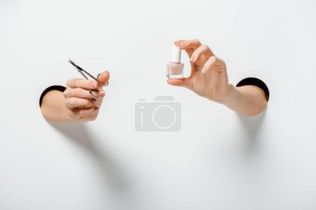 cropped image of woman holding nail scissors and nail polish for manicure in holes on white