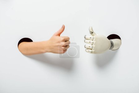 cropped image of woman and robot showing thumbs up through holes on white