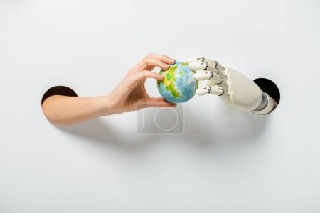 cropped image of woman and robot holding earth model through holes on white environment