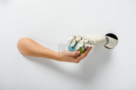 cropped image of woman with hand prosthesis holding earth model through holes on white