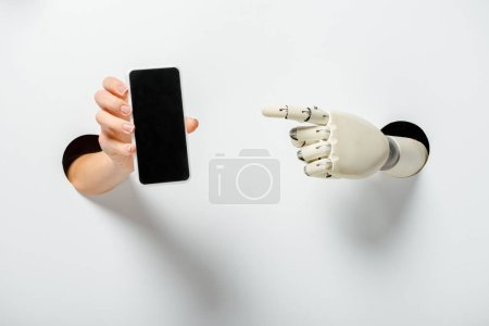 cropped image of woman holding smartphone with blank screen and robot pointing on it through holes on white