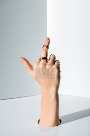 cropped image of woman showing middle finger with rings through hole on white